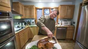 John Ross carves a roasted turkey at his