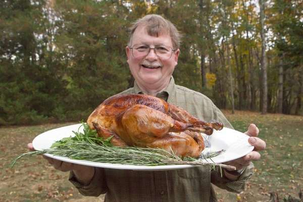 Chef John Ross holds a a slow-roasted, brined