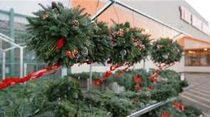 Christmas wreaths blow in the wind outside a