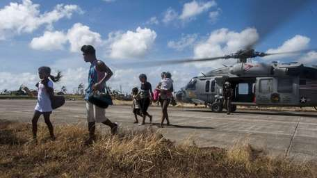 Filipino civilians exit an MH-60S Sea Hawk helicopter