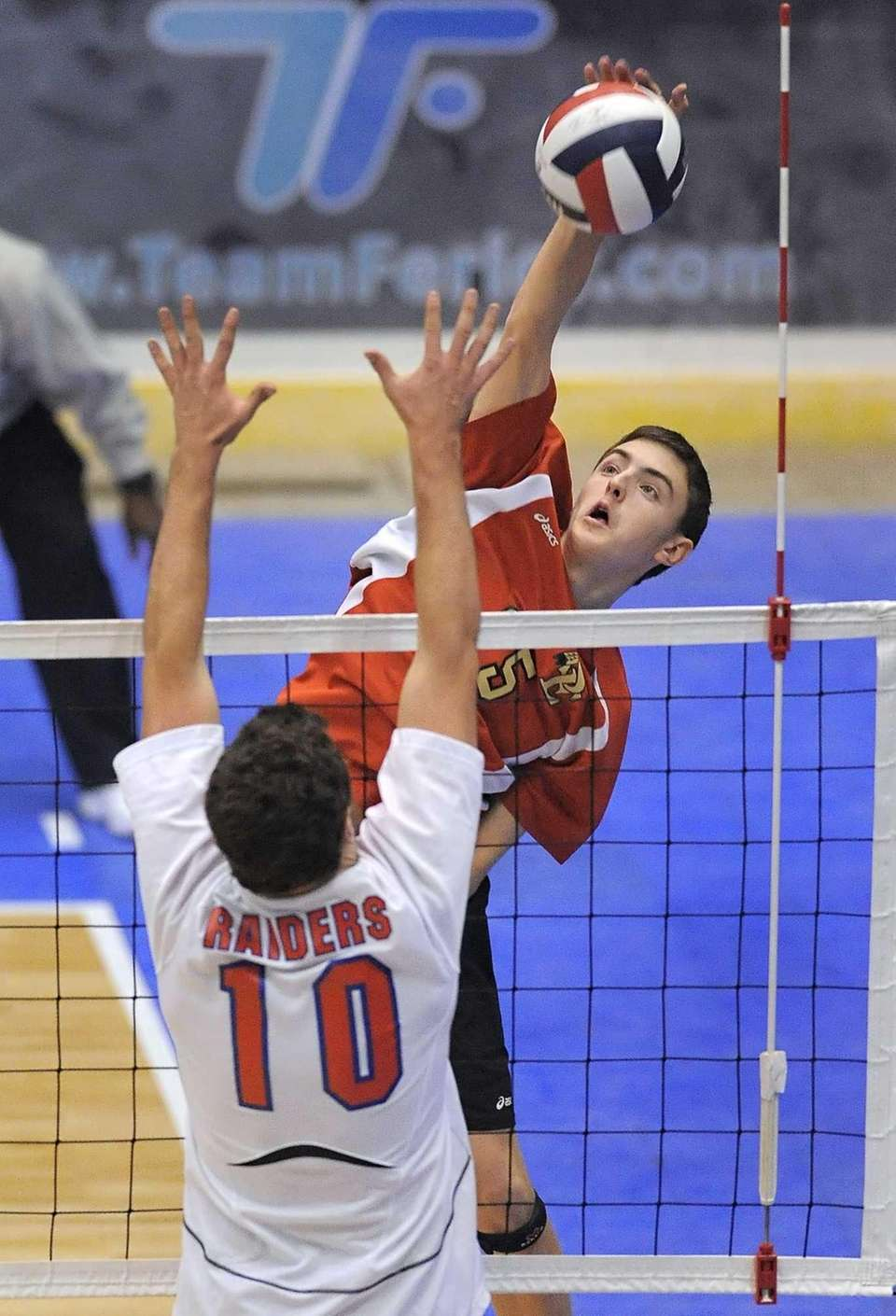 Sachem East's Sean Harrington, right, hits by the