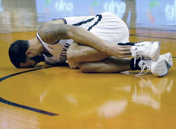 Nets' Deron Williams grabs his leg after being