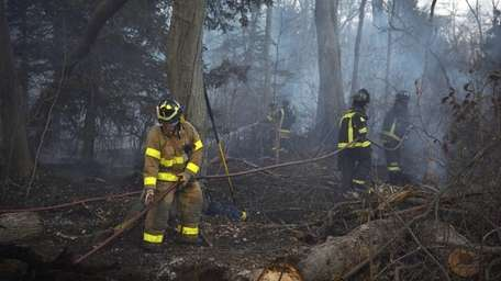 Firefighters drag connected hoses to the scene of