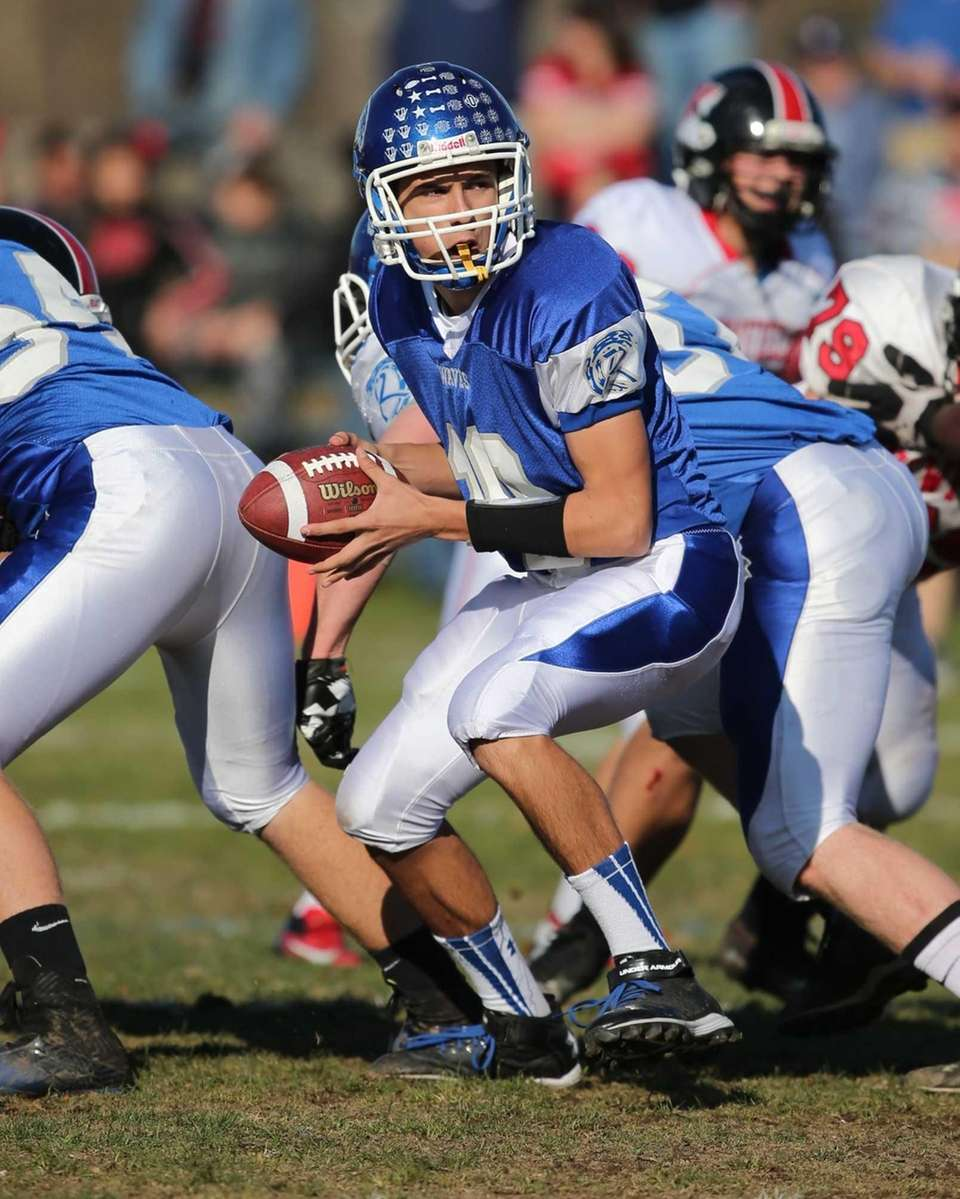 Riverhead quarterback Kenneth Simco looks to hand the