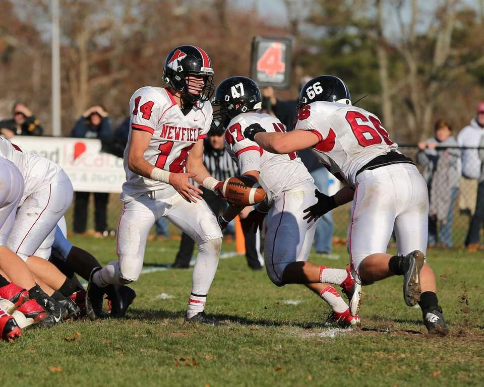 Newfield quarterback Dylan Harned (14) hands off to