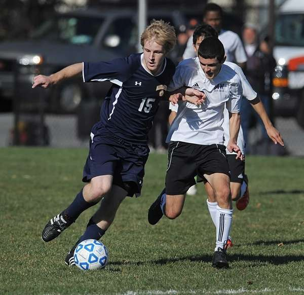 Massapequa's Chris McGrath, left, is pressured by Monroe-Woodbury's