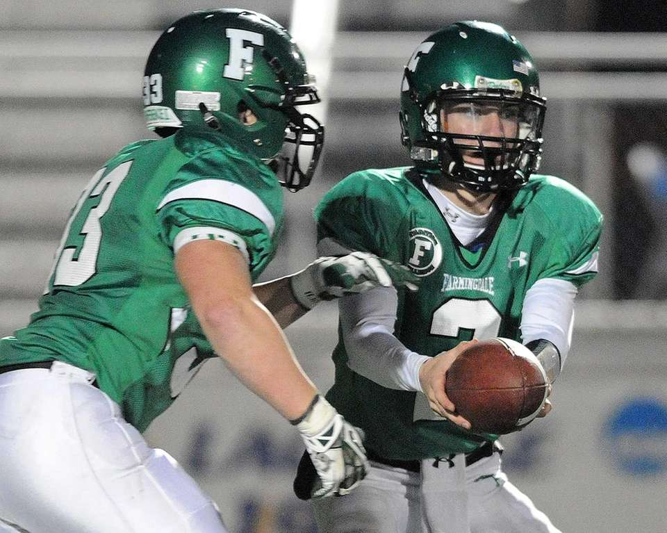 Farmingdale Vinny Quinn (right) hands off to teammate