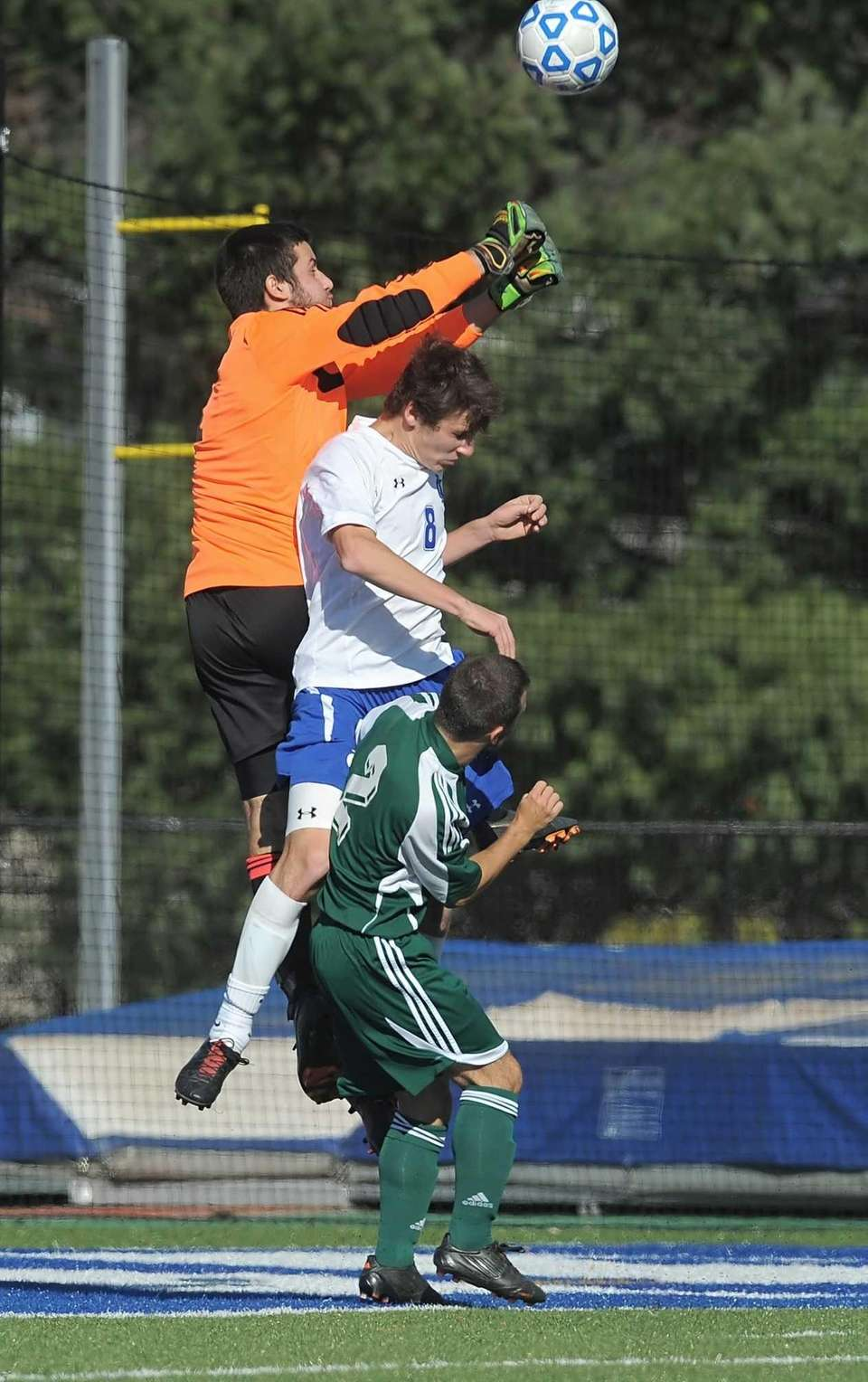 Carle Place's goalkeeper John Guzzo, top, punches the