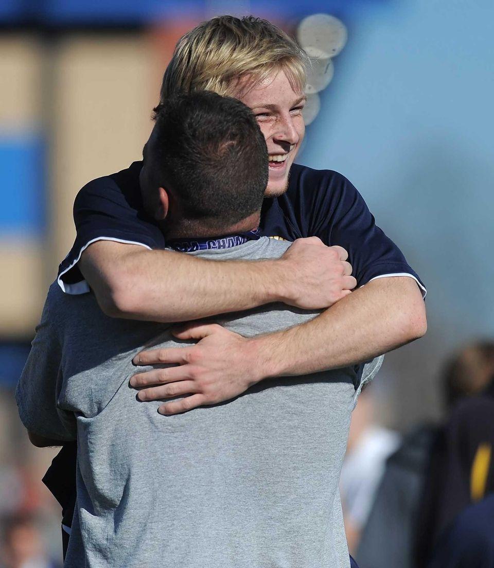 Massapequa's Chris McGrath hugs assistant coach Ken Wing