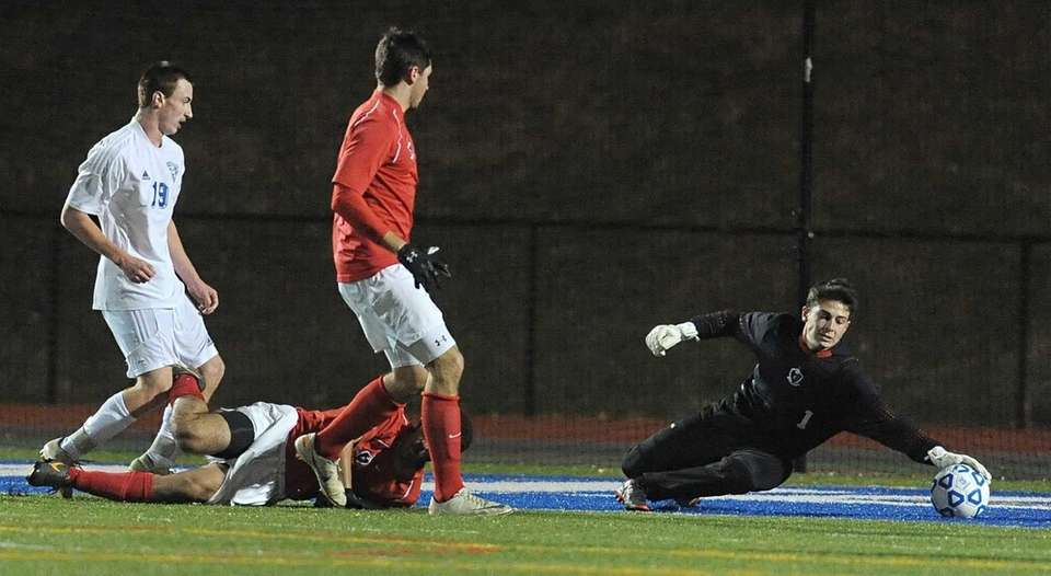 Friends Academy goalkeeper Brandon Rosenbaum, right, reaches to