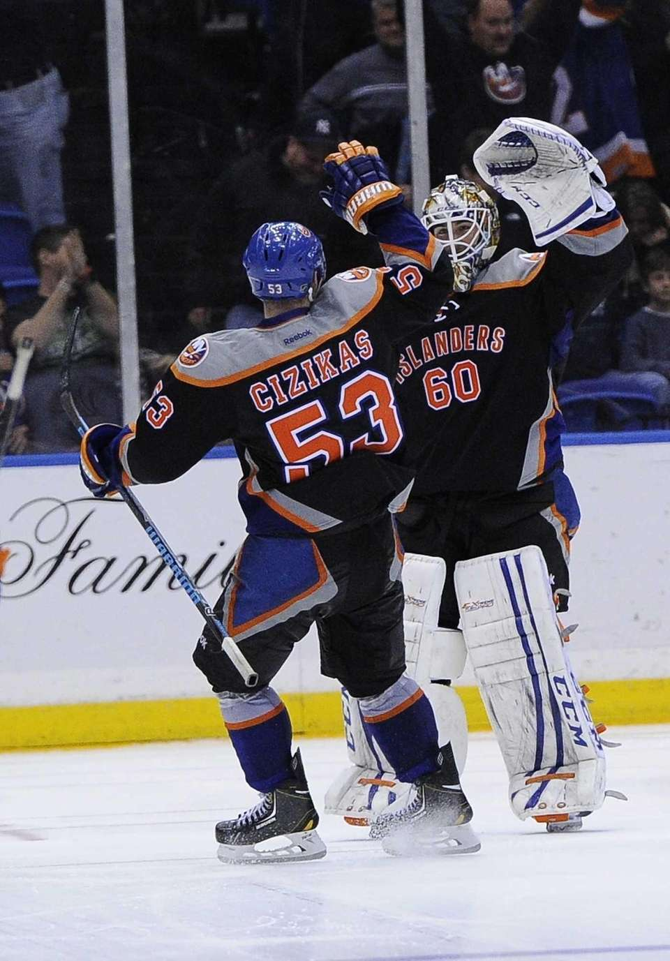 Islanders goalie Kevin Poulin is congratulated by Casey