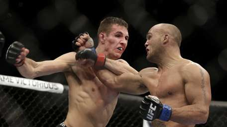 Rory MacDonald, of Canada, left, exchanges punches with