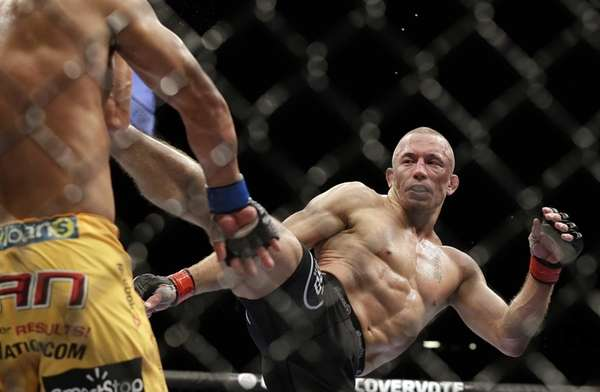 Georges St. Pierre, of Canada, kicks Johny Hendricks,