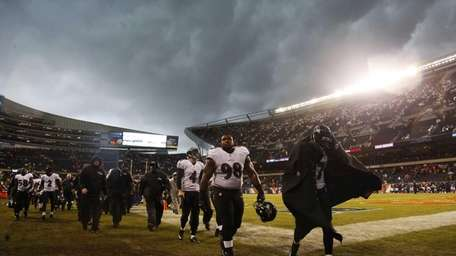 Baltimore Ravens players leave the field as play