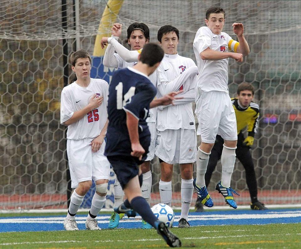 Massapequa's Dylan Nealis, front, puts a free kick