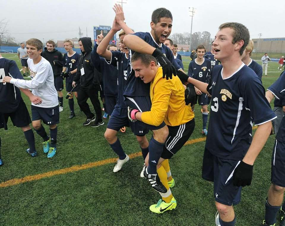 Massapequa's John Romano, top, is lifted by goalkeeper