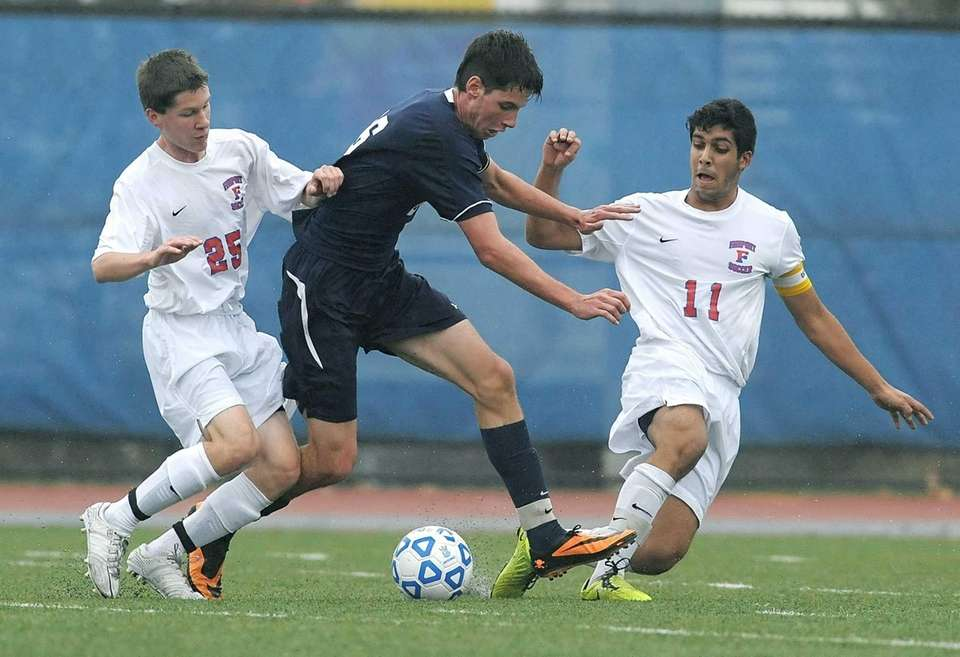 Massapequa's Sean Nealis, center, fights through the pressure