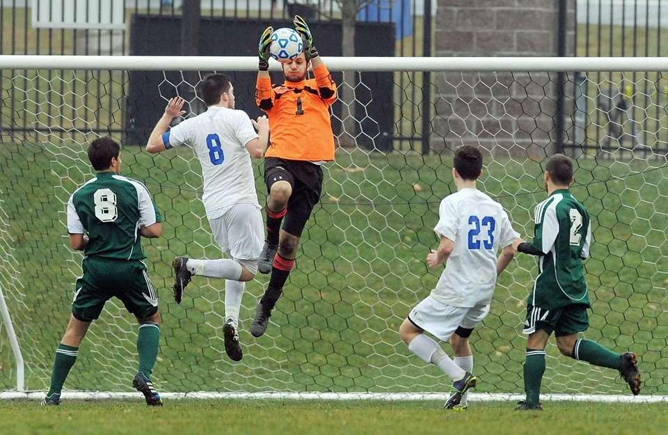 Carle Place goalkeeper John Guzzo, center, grabs the