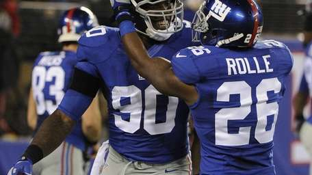 Jason Pierre-Paul is congratulated by safety Antrel Rolle