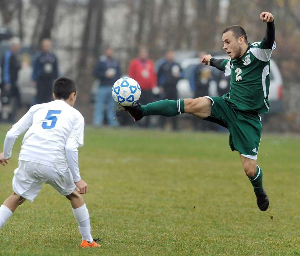 Carle Place's Eddie Cruz, right, jumps to get