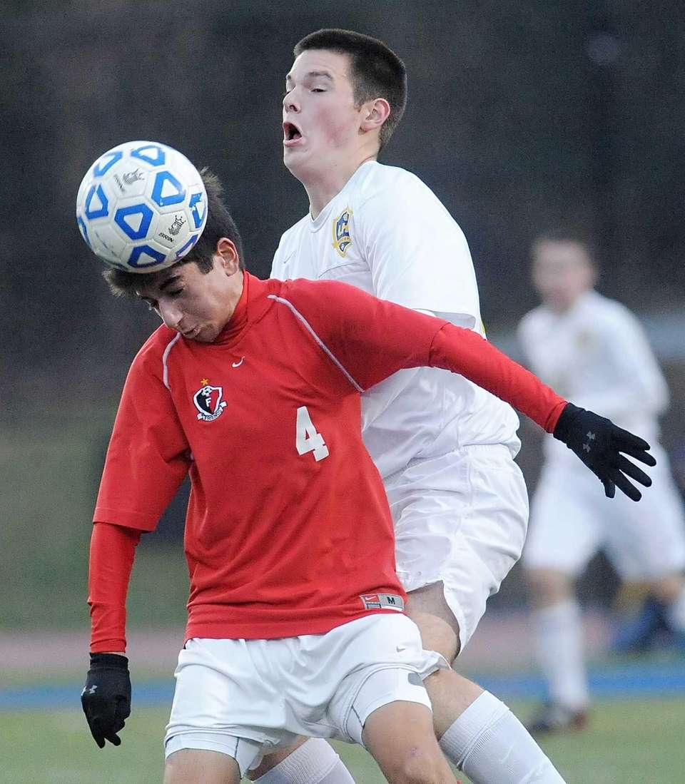 Friends Academy's Oliver Muran, left, gets to header