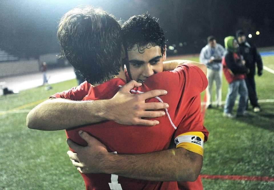 Friends Academy's Jonathan Nierenberg, facing, hugs teammate Maximilian