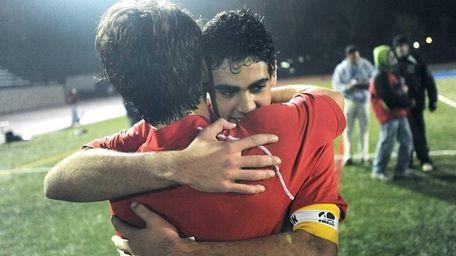 Friends Academy's Jonathan Nierenberg, facing, hugs teammate Maximilian