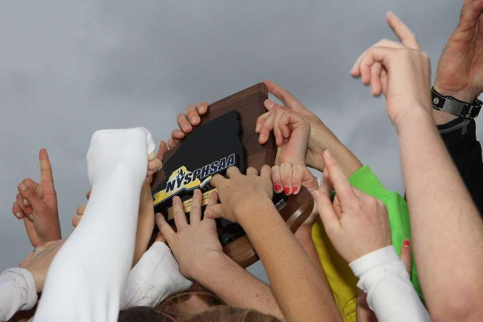 Garden City players touch the championship trophy after