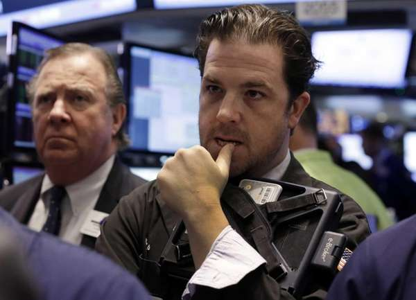 Trader Christopher Lotito, right, works on the floor