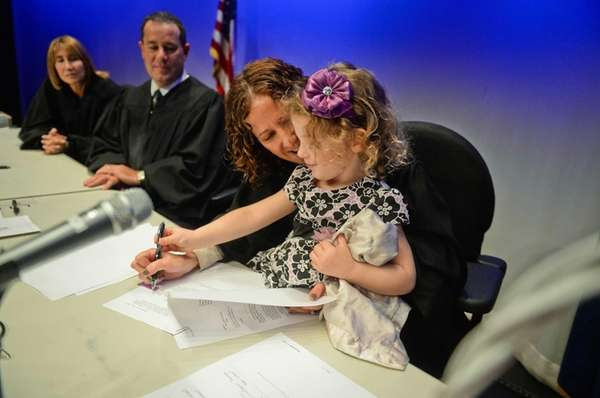 Judge Robin M. Kent assists Eleanor Haas-Colwell, 3,