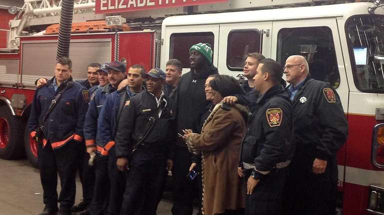 Jets' Muhammad Wilkerson, green hat, attends a charity