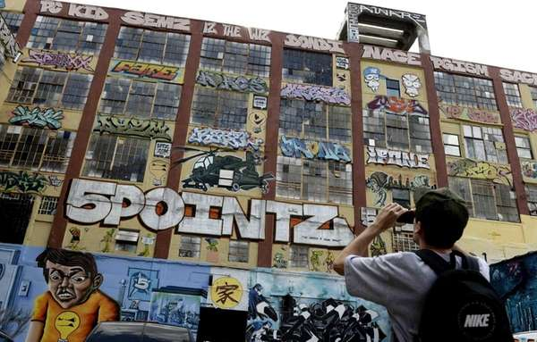 People look over the graffiti on a giant