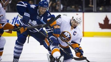 Toronto Maple Leafs' Jay McClement, left, battles for