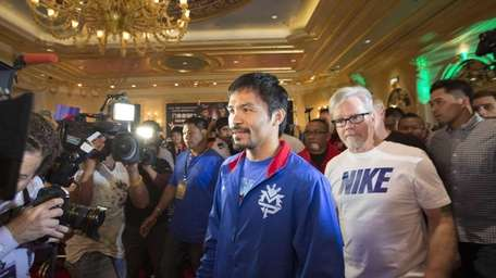 Manny Pacquiao, center,and his trainer Freddie Roach arrive
