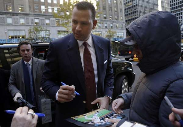 Alex Rodriguez signs autographs as he arrives at