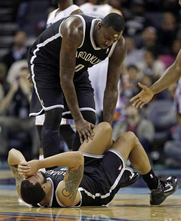 Deron Williams is helped by Andray Blatche after