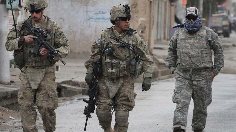 U.S. soldiers walk with their Afghan translator near