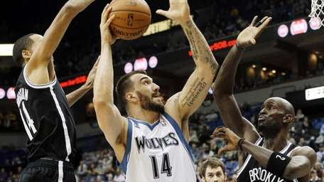Minnesota Timberwolves' Nikola Pekovic, center, attempts a shot