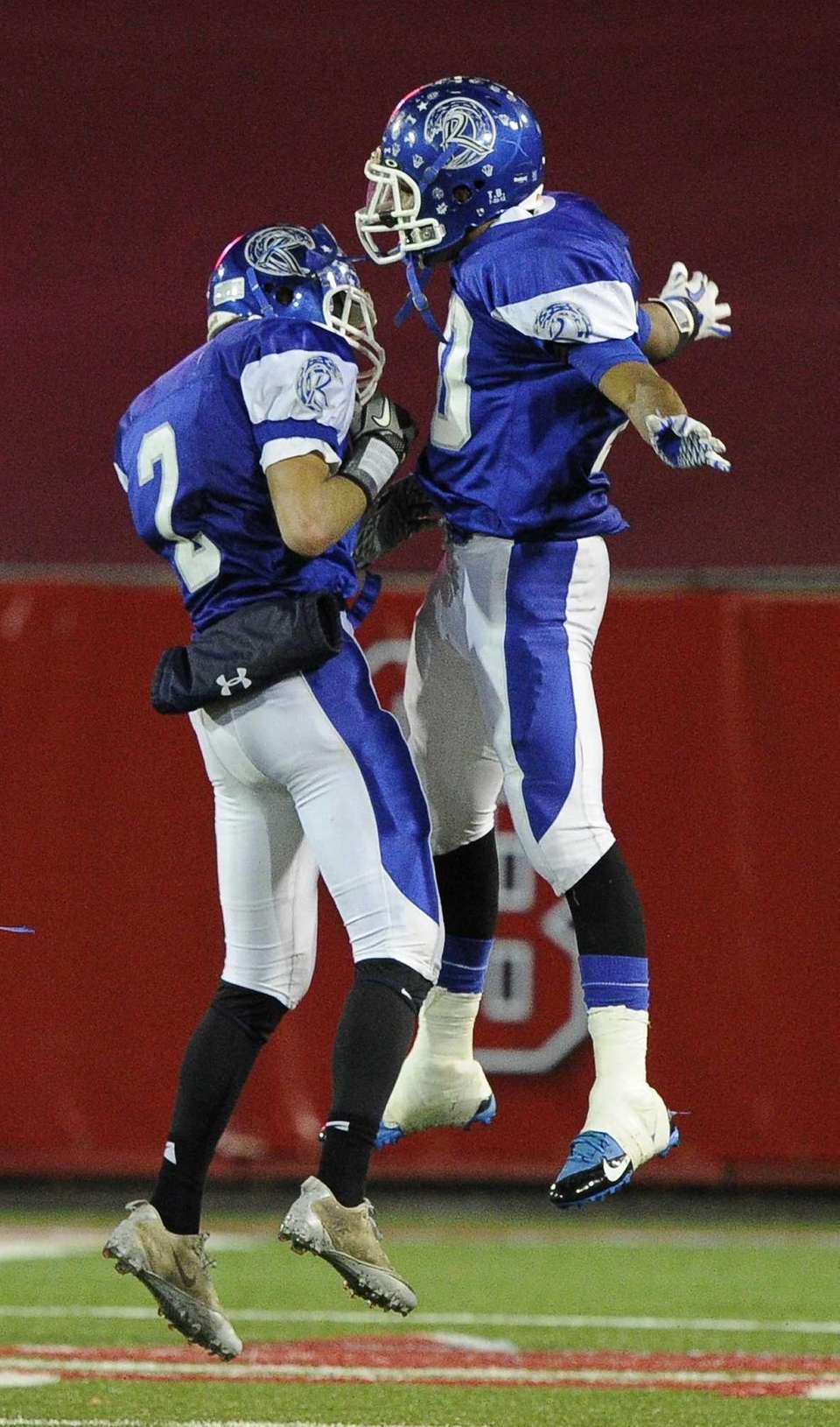 Riverhead's Ryan Hubbard, left, celebrates his interception run