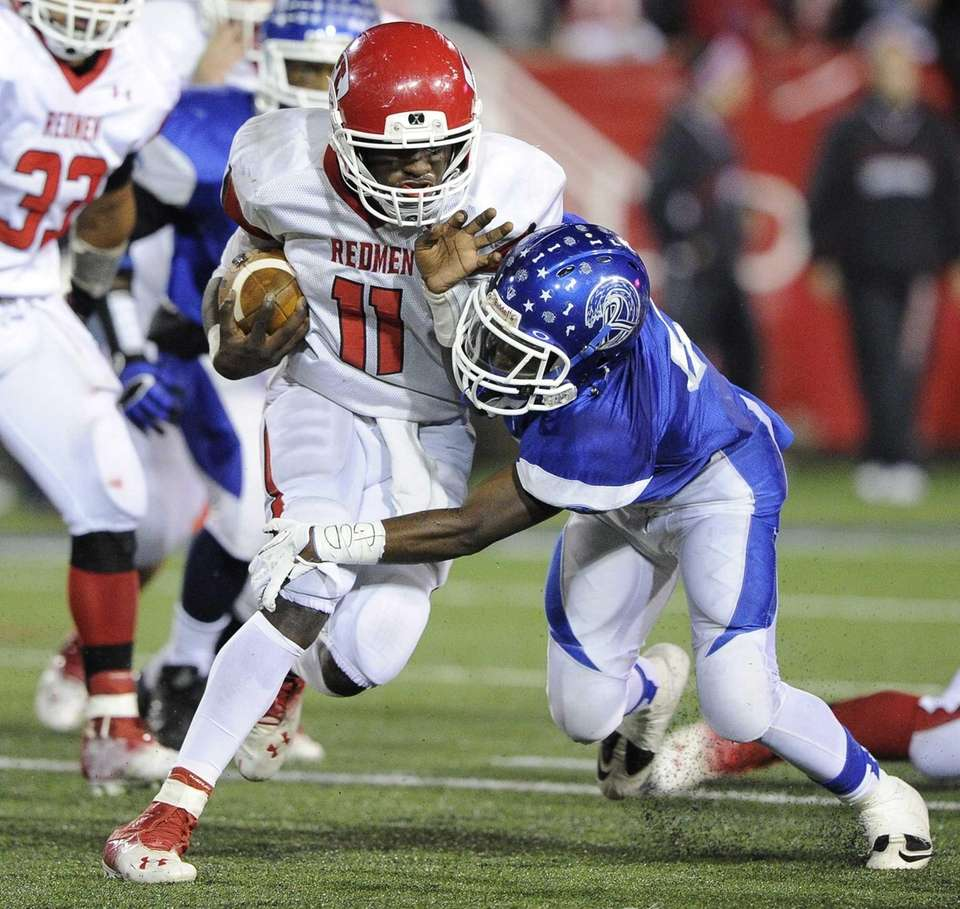 East Islip quarterback Hugens Tranquille is tackled by