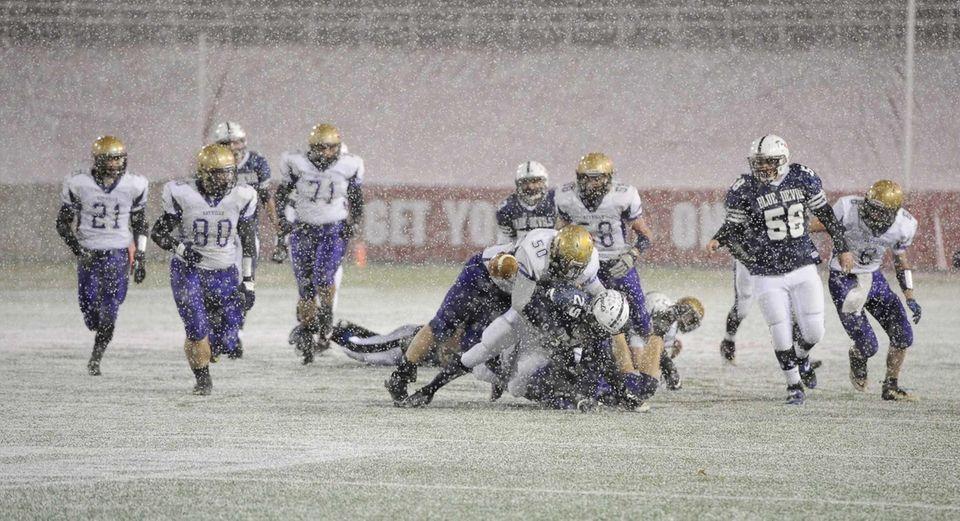 Huntington's Levar Butts fumbles the football as Sayville's