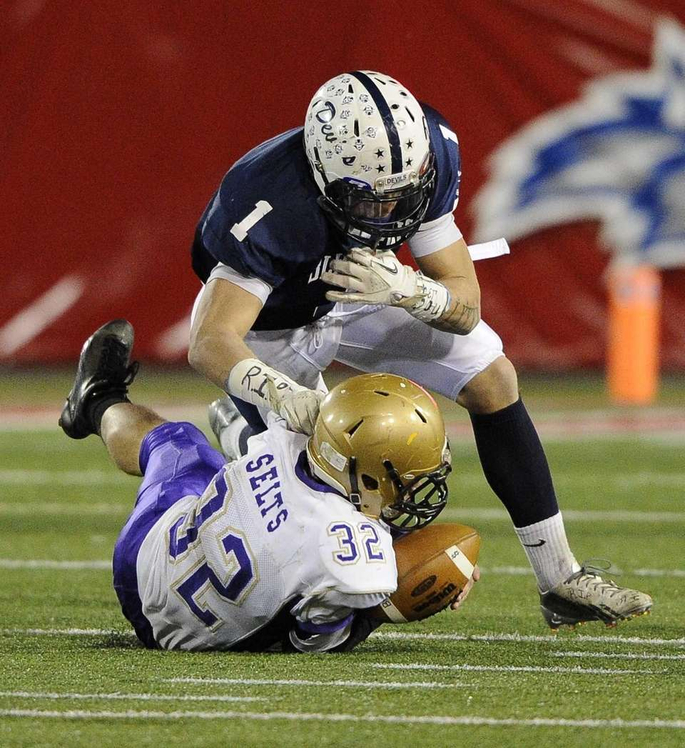 Sayville's Matthew Selts recovers a fumble by Huntington's