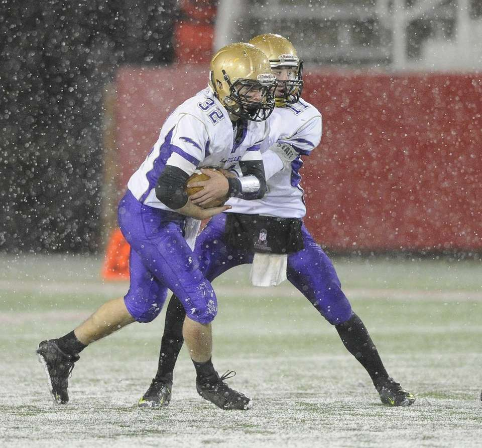 Sayville quarterback Jack Coan hands the football off