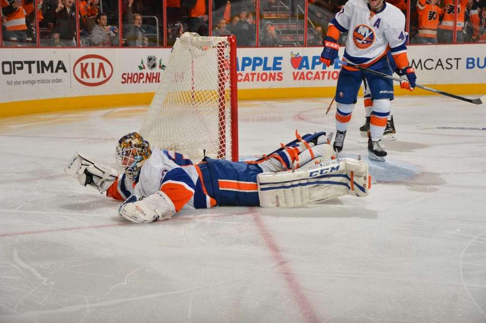 Islanders goaltender Kevin Poulin dives for the puck