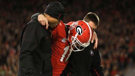 Georgia Bulldogs quarterback Aaron Murray (11) is helped