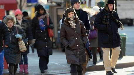 People cross a street in New York, as