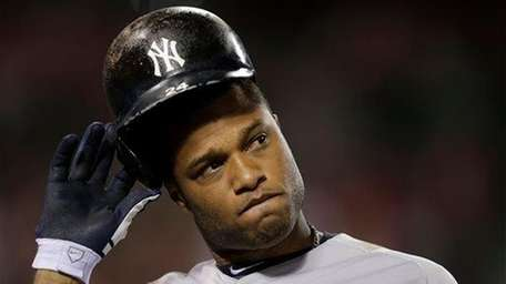 Robinson Cano takes off his helmet after he