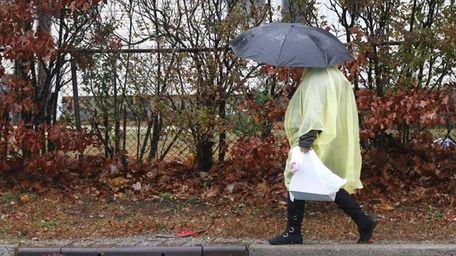 A woman walks under an umbrella in the