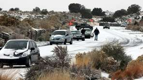 Cars slide on a road in Albuquerque, N.M.,