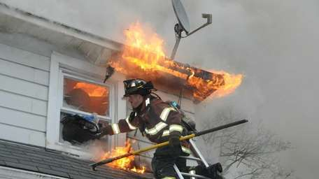 A North Babylon firefighter works to control a